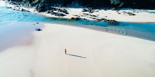 Drone image of person walking on Moonee Beach NSW