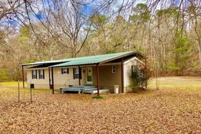 JOINS HNF!! TURN KEY CAMP WITH 2006 MH WITH 2 BED/ 2 BATH.  BEAUTIFUL LOT, CREEK, WATER WELL.