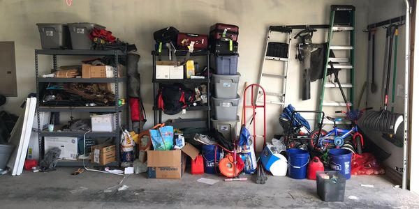 messy garage.  Disaster of a garage, cluttered and stuff all over the place.