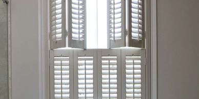 Tier on tier shutters for tall windows.  Traditional shutters look.  Shutters painted to match room.