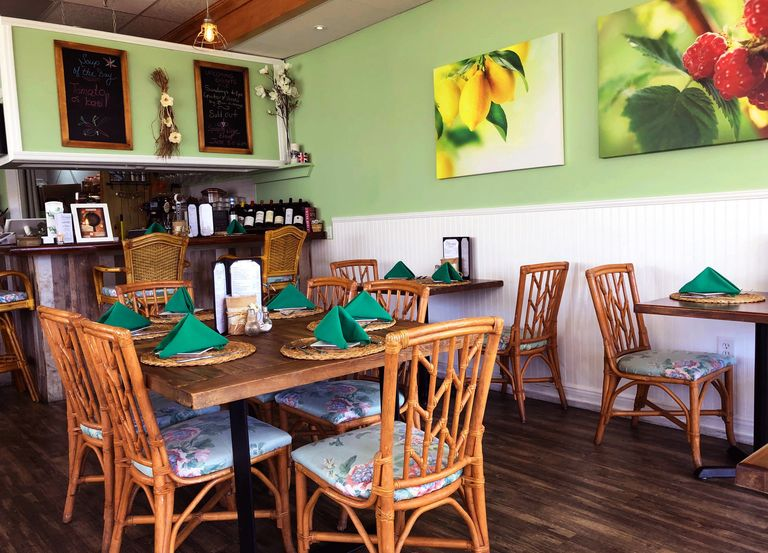 Photo of the Interior of Cremesh Restaurant. Green walls and rattan seating.