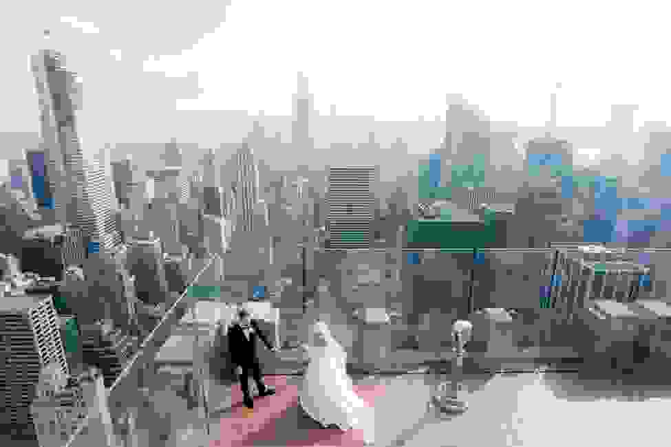 A bride and groom on their wedding day overlooking New York City skyscrapers.