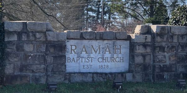 Stonework sign reading Ramah Baptist Church Est. 1828 in focus with grass and trees surrounding it.