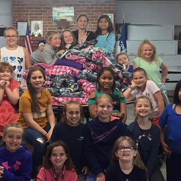 Girl Scouts help cut fleece for blankets for the pound.