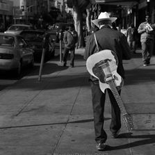 Man in black texts, guitar on back, with cowboy hat, Mission District, San Francisco