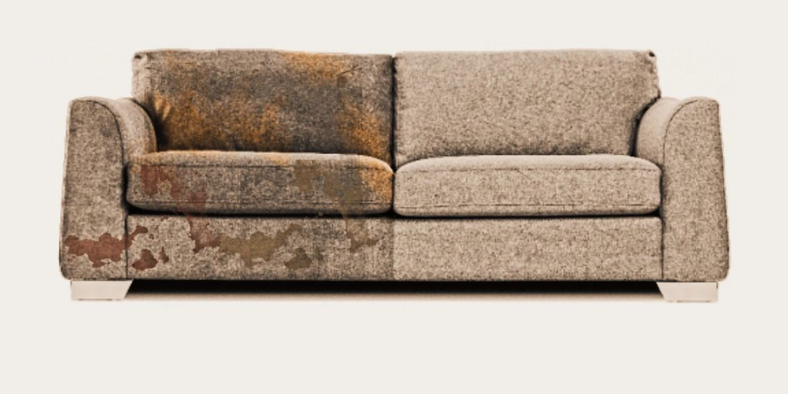 Sofa that is filthy on the left half and has had professional upholstery cleaning on the other half.