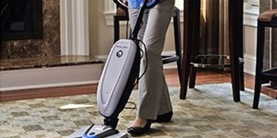 female vacuuming the carpet before it is cleaned