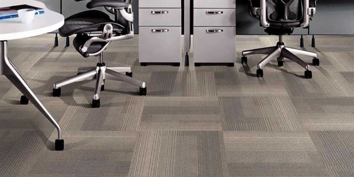 Office chairs, filing cabinets, and a table on grey colored commercial carpet tiles.