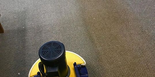 man cleaning carpet in a commercial office