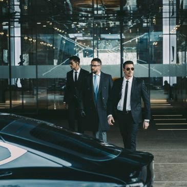 Two bodyguards walking with executive client