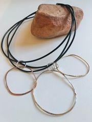 "FLO Choker    $45    18"" black leather with signature 'flo' pendant Sterling, gold f, bronze"