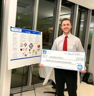 Benjamin McEvoy poses with his check after his win at the UMass Lowell DifferenceMaker competition.