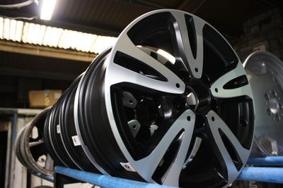 Black and silver refurbished wheels in workshop at spit and polish.