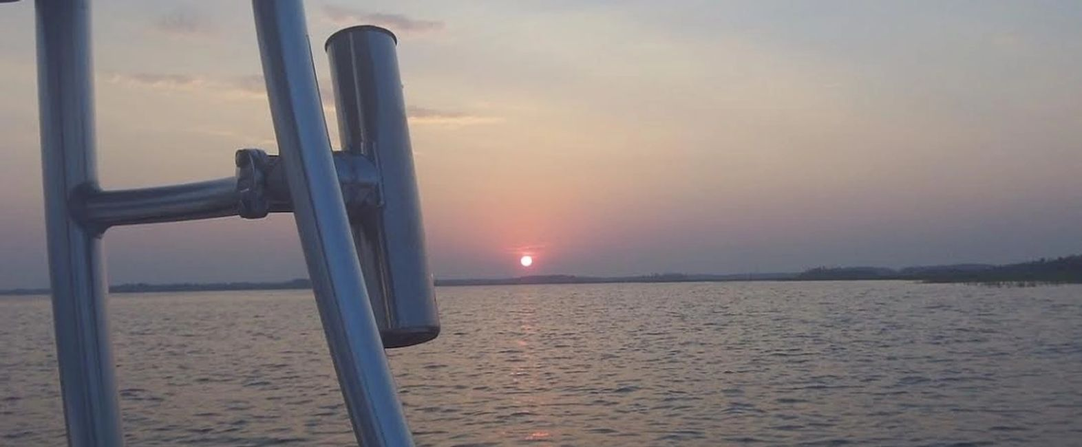 sunset and fishing rod holder on the Wando River
