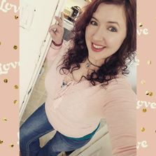Selfie of woman in pink shirt and blue jeans