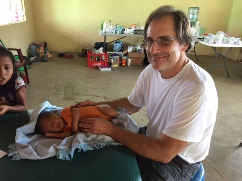 Daniel working on a child on a mission trip in Belize, Central America