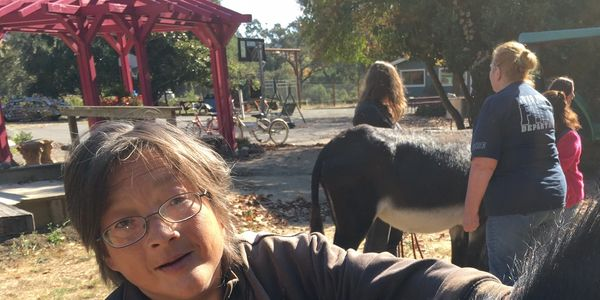 Jeffrey Wong, an artist in the Vine Village Arts day program, petting Dawn the Donkey.