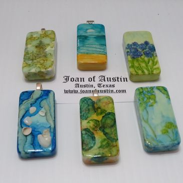 Samples of Alcohol Ink on Dominoes to be worked into necklaces or worn as pendants.