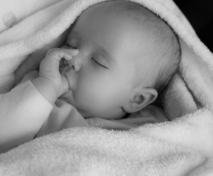An infant, swaddled in a soft white blanket, sleeps while sucking her thumb.
