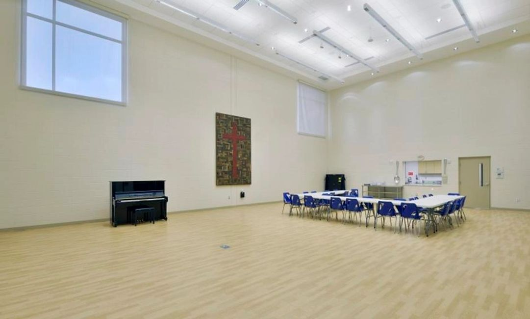 A large, gymnasium-type room with a high ceiling, white walls, and chairs and tables. A piano and cr