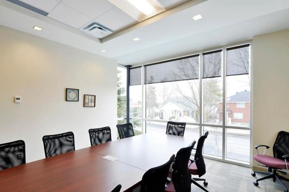 A large, dark boardroom table with swivel chairs around it sits in front of a huge, bright window.