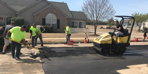 paving company repairing damaged pavement and potholes in a parking lot or driveway near Memphis, TN