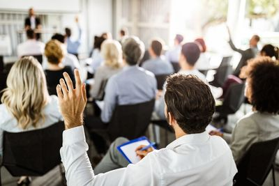 Back view of a businessman raising his hand on a seminar