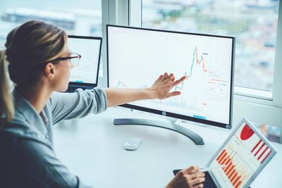Business woman studying graph on monitor