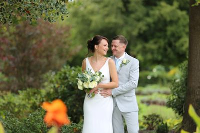 bride and groom smiling at each other in garden