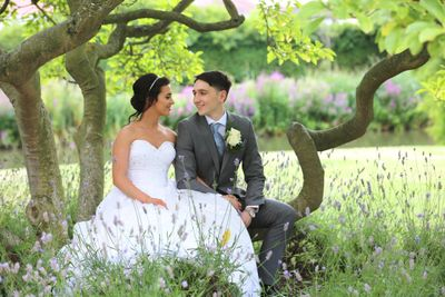 bride and groom looking at each other sitting on a tree branch