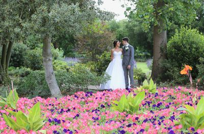 bride and groom behind flower bed