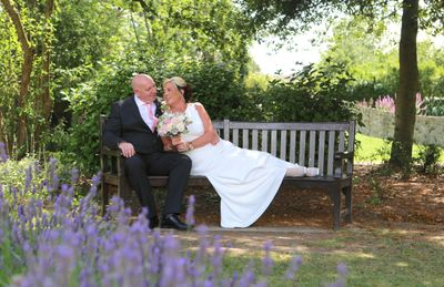 bride lying on park bench next to groom