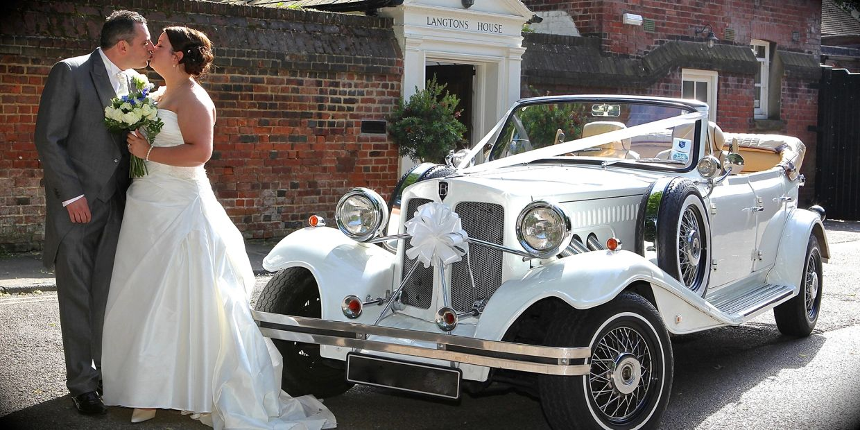 couple kissing in front of vintage Beauford wedding car