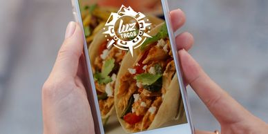 a person holding a phone showing Luz Tacos App on the screen to order Mexican food online