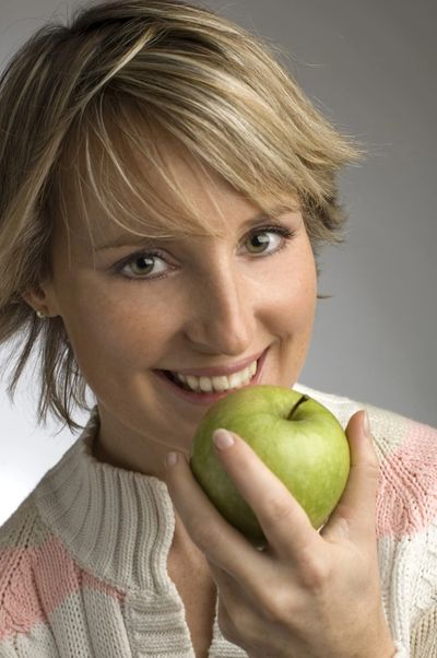 Woman with beautiful teeth eating a green apple