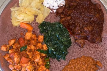Combination of lamb and chicken with three veggies on Ethiopian bread
