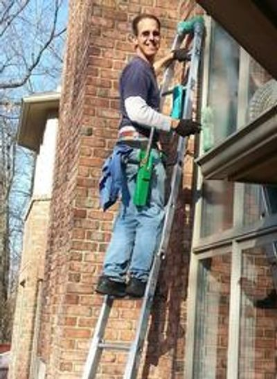 Owner Steve Dickson cleaning window on a ladder