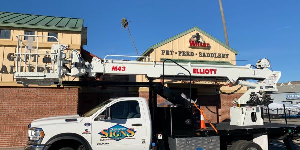 Sign installation truck. Sign installer storefront signs. LED channel letters. Wall sign 3D letters