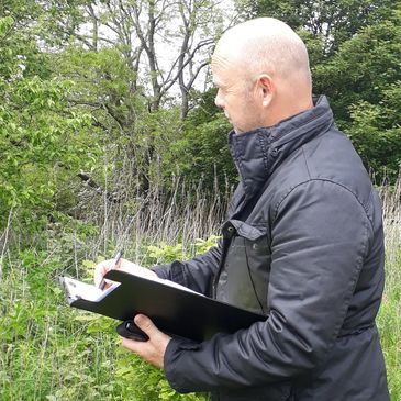 Man with clipboard collecting data about trees