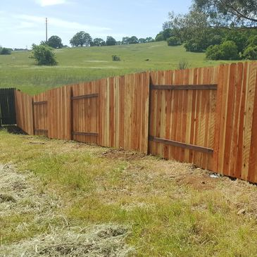Redwood Dog Ear Fence with pressure-treated rails and steel posts in Cameron Park, CA.