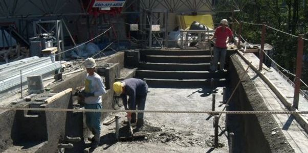 SLI Shotcrete workers finishing smoothing out concrete on a commerical pool.