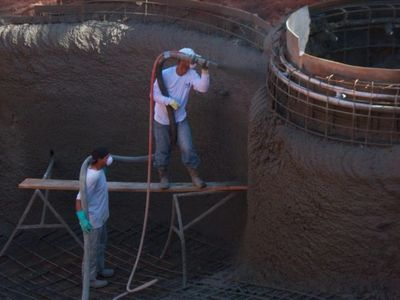 An SLI Shotcrete employee shooting concrete.