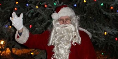 Santa stands and waves by the tall tree strung with Christmas lights at the Littleton Museum's Holiday's Eve.