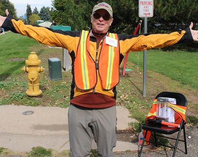 A volunteer with outstretched hands stands at the corner of the Craft Fair in Littleton.