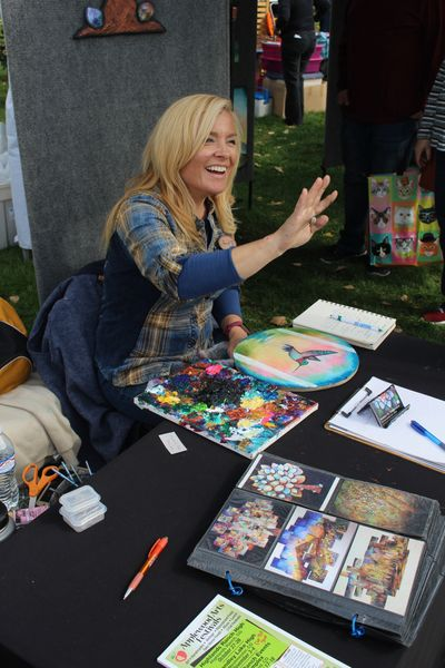 A crafter waves at someone while selling crafts at the Littleton Craft Fair.