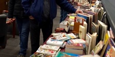 Three patrons peruse tables of books for sale for the Friends of the Library and Museum's Used Book Sale at Bemis Library in Littleton.