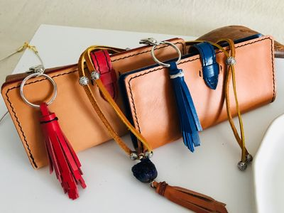 The Charlotte ladies leather wallet, with red and blue leather tassels and a custom ladies leather necklace.
