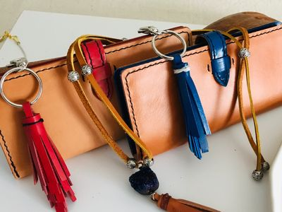 Ladies leather wallet pictured with leather tassel and custom leather necklace. In red and blue.