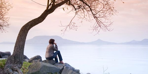 Woman looking across the lake in contemplation. Nature surrounds her to represent wellness