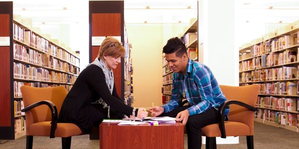 Woman teaching young man while sitting in library